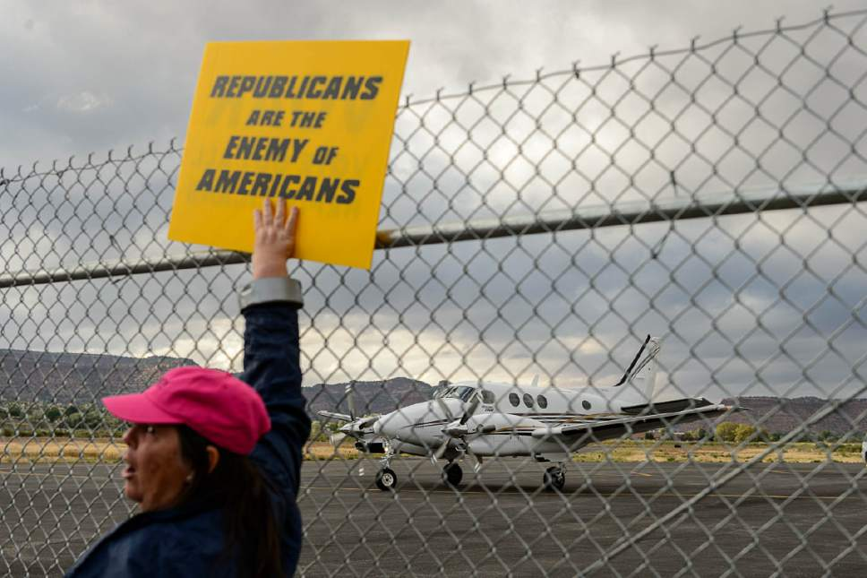 "Trent Nelson  |  The Salt Lake Tribune A protestor holds up a sign reading, ""Republicans are the enemy of Americans"" as a plane prepares to deaprt following a news conference by Secretary of the Interior Ryan Zinke at the Kanab Airport, Wednesday May 10, 2017."