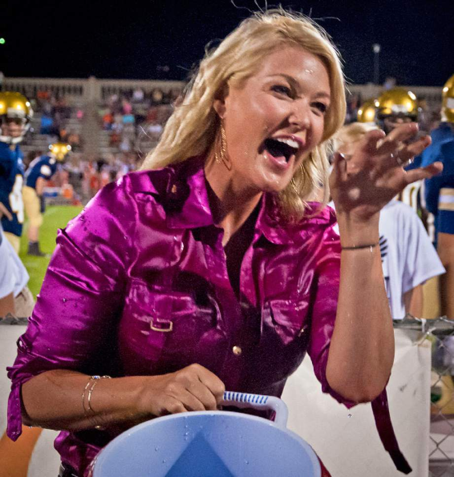 Michael Mangum  |  Special to The Salt Lake Tribune  KUTV 2News reporter Shauna Lake laughs with excitement after dumping a bucket of ice water over Tribune columnist Robert Kirby during halftime of the Homecoming football game at Skyline High School on Friday, September 19, 2014.