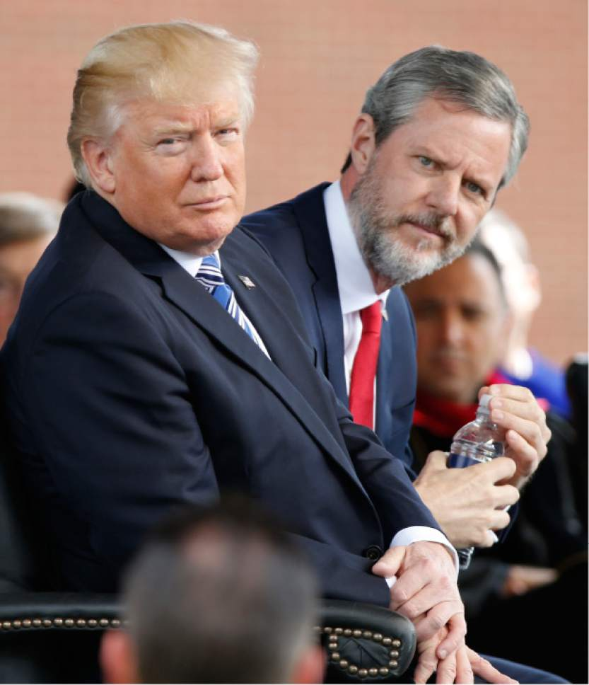President Donald Trump, left, and Liberty University president, Jerry Falwell Jr., right, listen to music during commencement ceremonies at the school in Lynchburg, Va., Saturday, May 13, 2017. (AP Photo/Steve Helber)