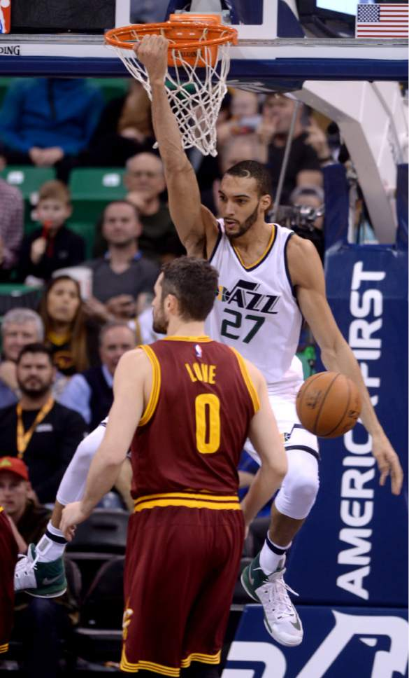Steve Griffin / The Salt Lake Tribune  Utah Jazz center Rudy Gobert (27) hangs on the rim after slamming the ball for two during the Utah Jazz versus Cleveland Cavaliers NBA basketball game at Vivint Smart Home Arena in Salt Lake City Tuesday January 10, 2017.