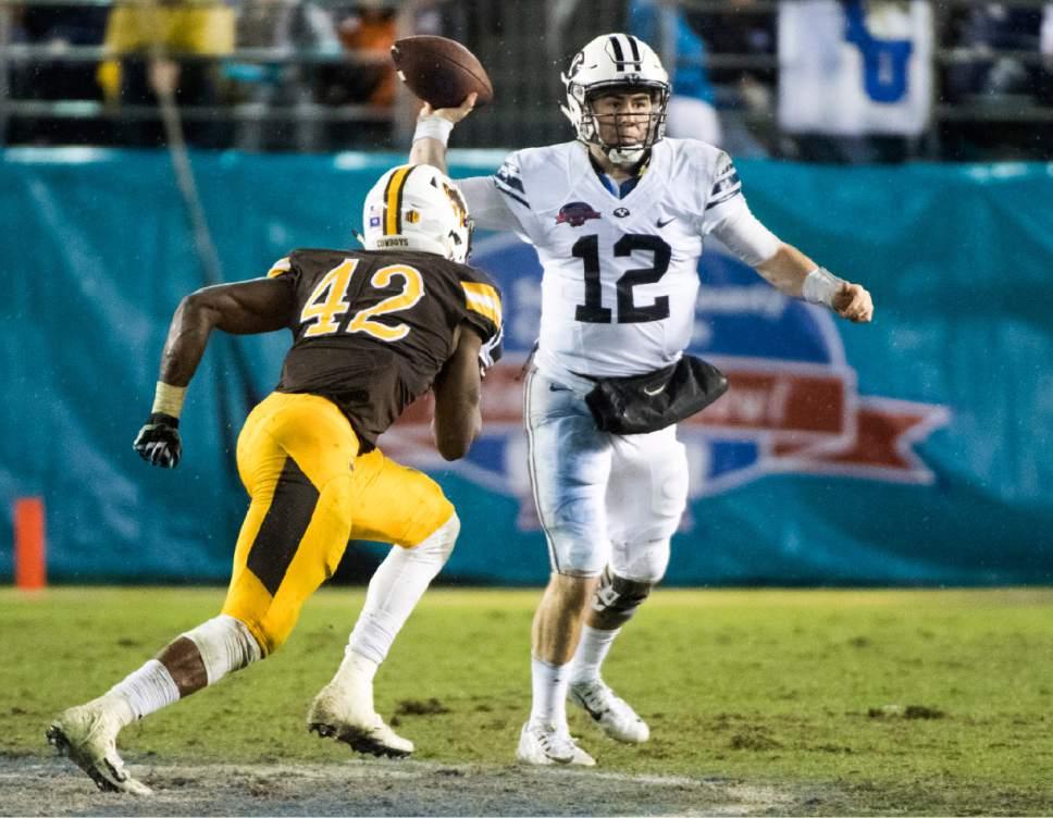 Rick Egan  |  The Salt Lake Tribune  Brigham Young Cougars quarterback Tanner Mangum (12) looks for an open man, in the Poinsettia Bowl, at Qualcomm Stadium in San Diego, December 21, 2016.