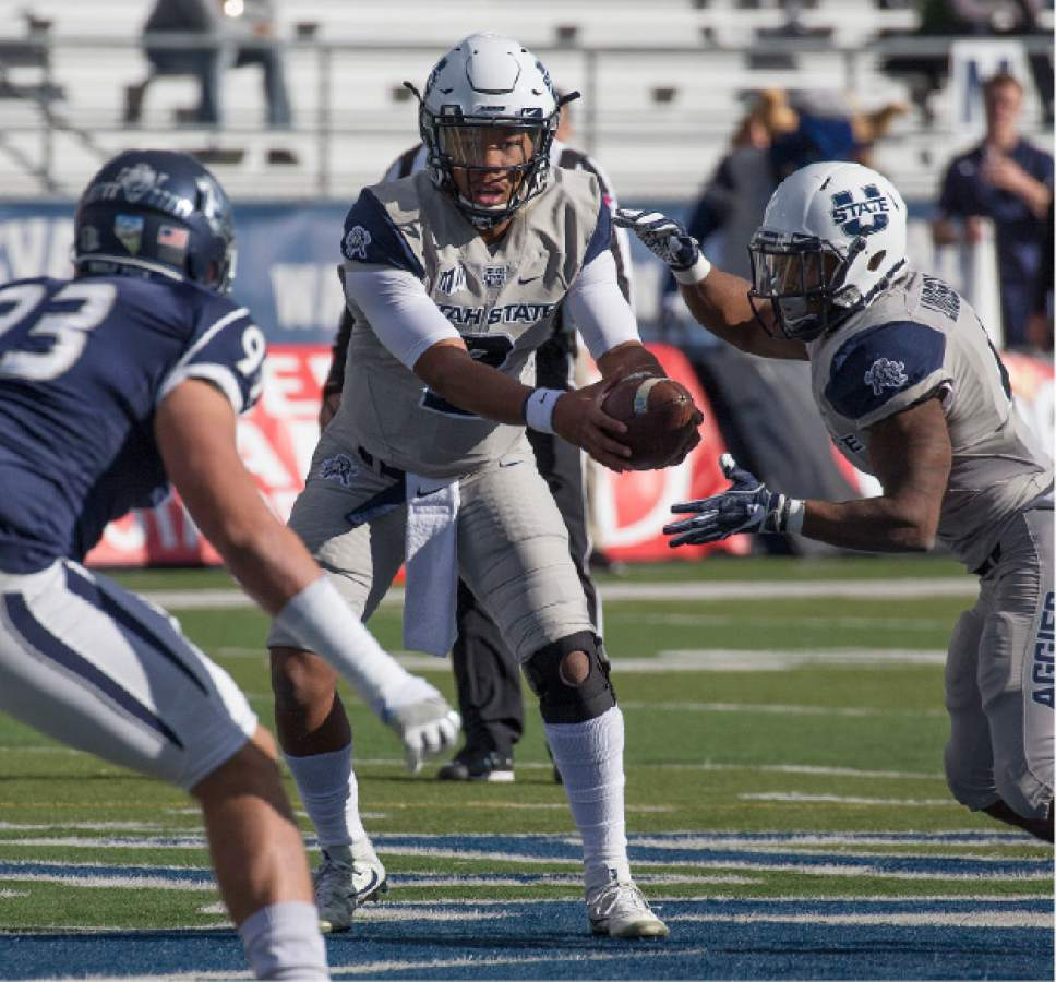 Utah State quarterback Kent Myers hands off to running back Tonny Lindsey against Nevada in the first half of an NCAA college football game on Saturday, Nov. 19, 2016, in Reno, Nev. (AP Photo/Tom R. Smedes)
