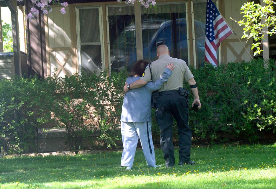 Al Hartmann  |  The Salt Lake Tribune Weber County sheriff's deputy comforts a neighbor as they continue to investigate a homicide at a residential home in the 7400 East block of 400 South in Huntsville Thursday morning May 11.