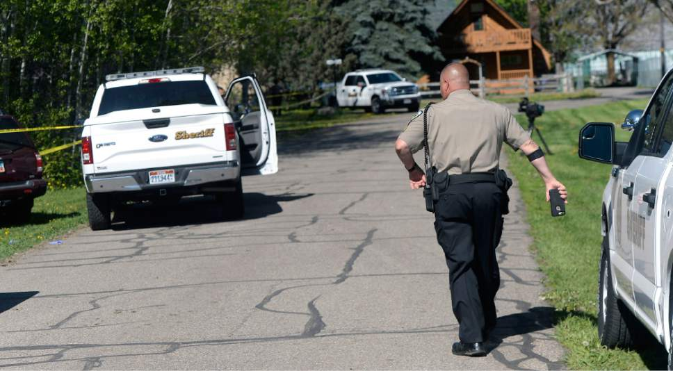 Al Hartmann  |  The Salt Lake Tribune Weber County sheriff's deputies investigate a homicide at a residential home in the 7400 East block of 400 South in Huntsville Thursday.