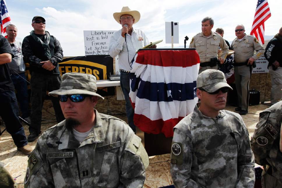 FILE - Rancher Cliven Bundy, middle, addresses his supporters with Clark County Sheriff Doug Gillespie, right, on April 12, 2014. Former Bureau of Land Management director Bob Abbey says Bundy supporters who threatened BLM employees during an armed standoff over the rancher's cattle should be held accountable. (AP Photo/Las Vegas Review-Journal, Jason Bean)