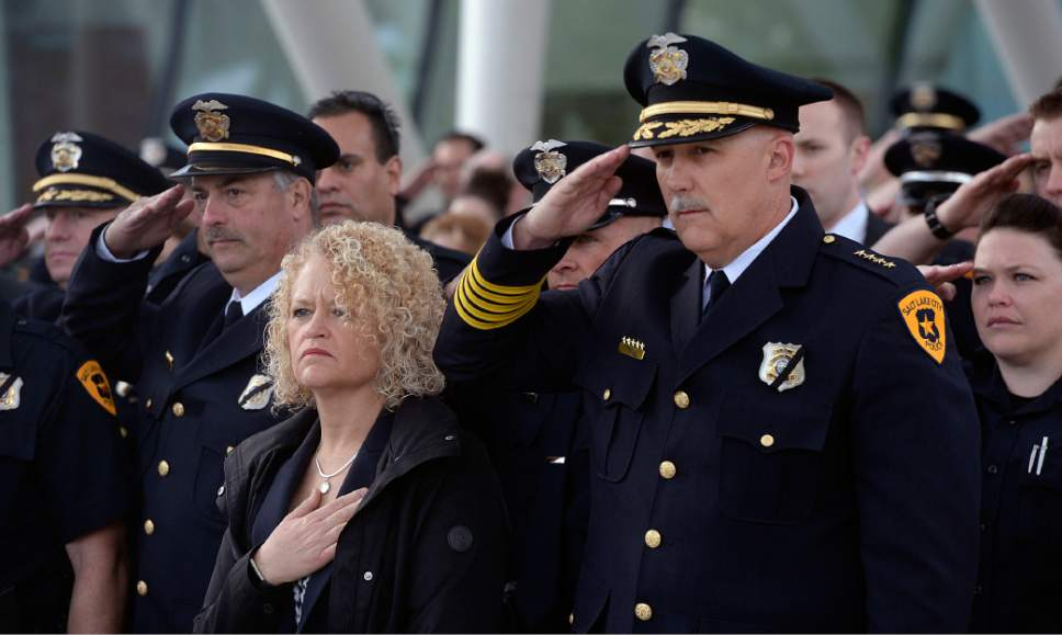 Al Hartmann  |  The Salt Lake Tribune Salt Lake City Mayor jackie Biskupski, left, and Salt Lake Police Chief Mike Brown salute with officers and family members during flag raising ceremony to honor and pay tribute to Salt Lake City's fallen police officers over the years at a memorial sunrise service Tuesday May 16.