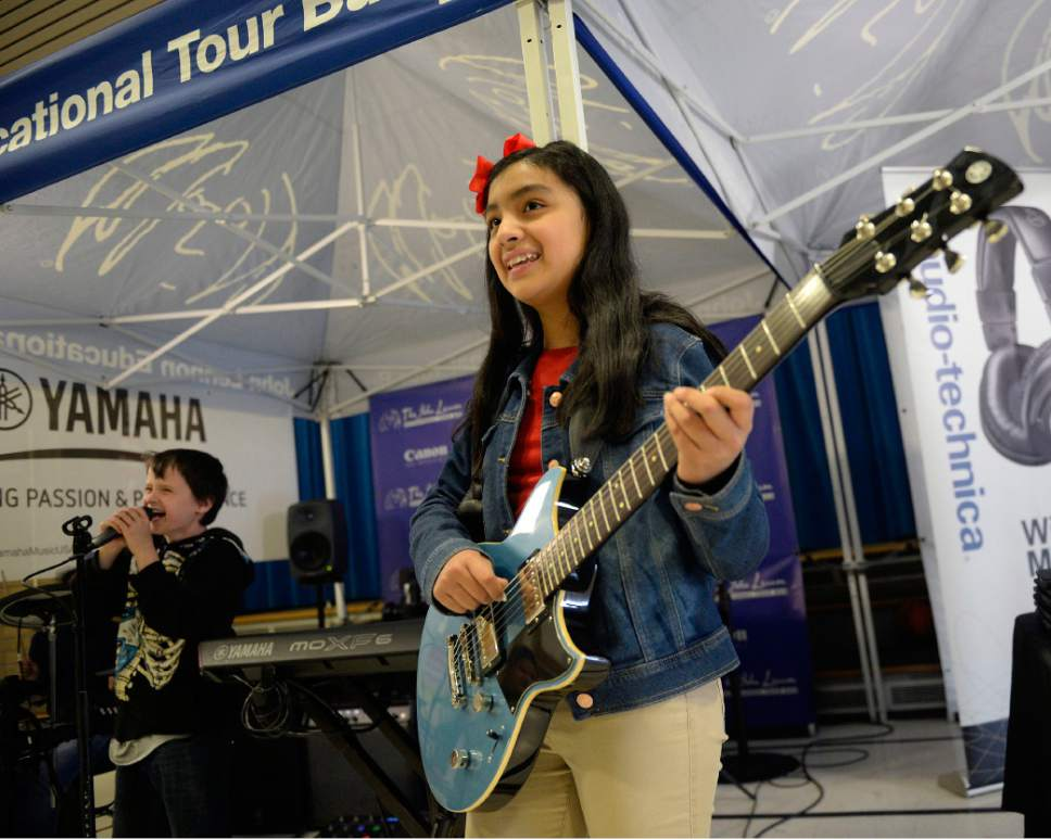 Al Hartmann  |  The Salt Lake Tribune Jackson Elementary fourth grader Kasey Morgan belts out vocals, left, and Valentina Denino-Guzman plays guitar to create their own song Wednesday, May 17.  The music can then be edited and produced on the John Lennon Educational Tour Bus containing a state-of-the-art mobile audio, video and live production facility.   In its 20th year, with the very newest technology and gear, the bus provides young people with career development tours of the studios and offers free digital media production workshops. In the workshops, assisted by three on-board engineers, students learn how to write, record, and produce original songs, music videos, documentaries, and live multi-camera video productions, using the most up-to-date  IT Solutions .
