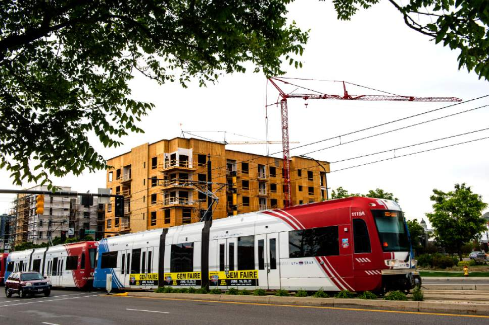 Chris Detrick  |  Tribune file photo A TRAX train zips past apartment construction along 400 South and 500 East in 2015. Utah Transit Authority officials want the public to know more about board members' potential conflicts of interest but does now want to release the disclosure forms that miht reveal whether an agency vote on a given project could benefit a board memeber.
