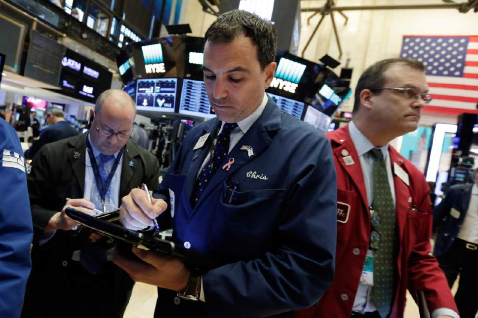 Trader Christopher LaGana, center, works on the floor of the New York Stock Exchange, Wednesday, May 17, 2017. Stocks are opening lower on Wall Street as banks and industrial companies fall. (AP Photo/Richard Drew)