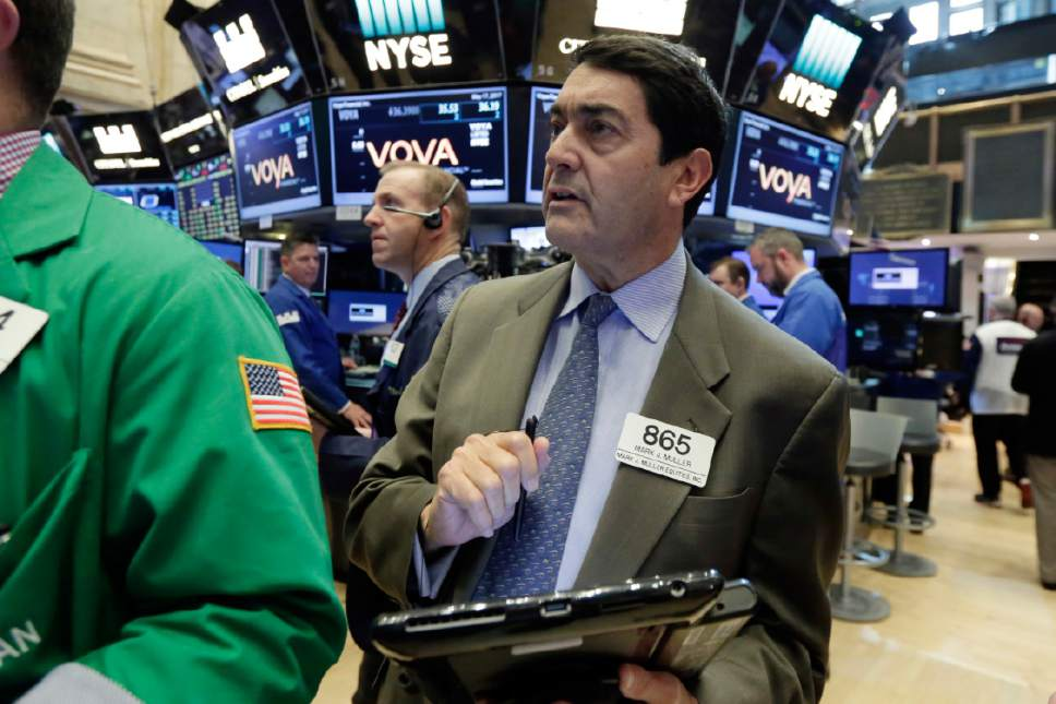 Trader Mark Muller, right, stands on the floor of the New York Stock Exchange, Wednesday, May 17, 2017. Stocks are opening lower on Wall Street as banks and industrial companies fall. (AP Photo/Richard Drew)