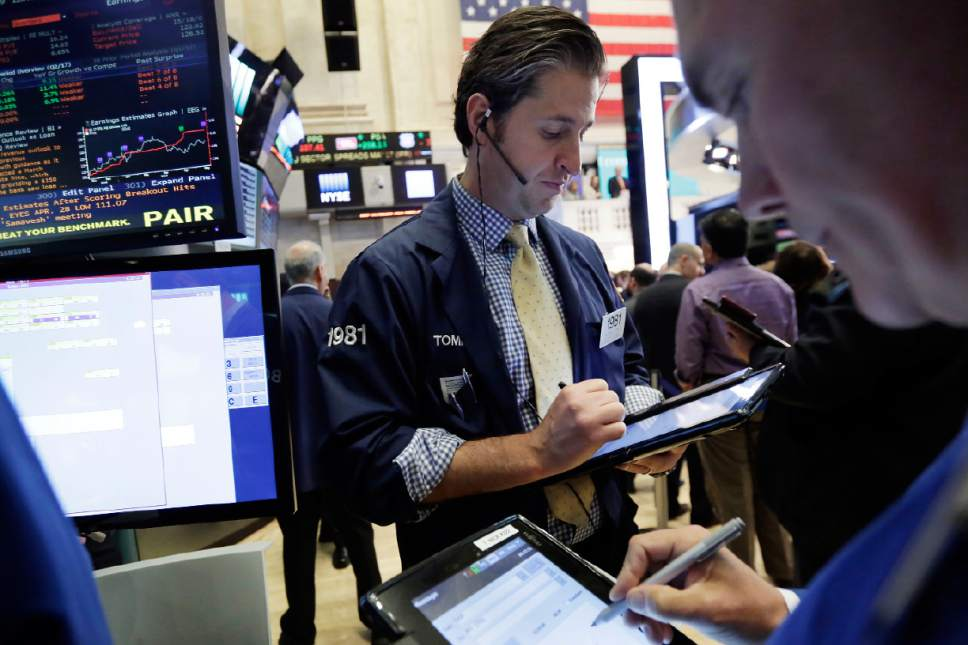 Trader Thomas Donato, center, works on the floor of the New York Stock Exchange, Wednesday, May 17, 2017. Stocks are opening lower on Wall Street as banks and industrial companies fall. (AP Photo/Richard Drew)