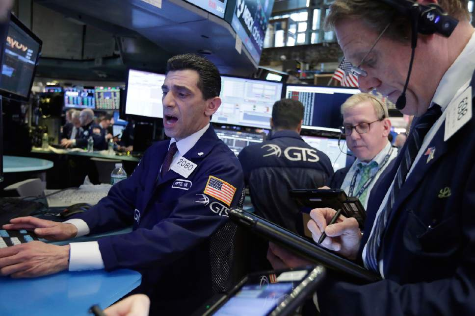 Specialist Peter Mazza, left, works with traders on the floor of the New York Stock Exchange, Wednesday, May 17, 2017. Stocks are opening lower on Wall Street as banks and industrial companies fall. (AP Photo/Richard Drew)