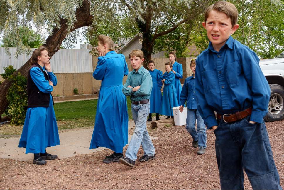 Trent Nelson  |  The Salt Lake Tribune FLDS women and children stand in the yard of their Colorado City, AZ, home as they are evicted, Tuesday May 9, 2017.