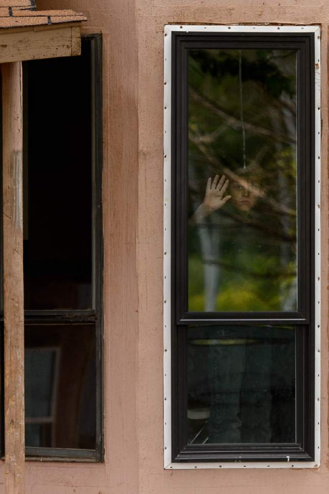Trent Nelson  |  The Salt Lake Tribune An FLDS boy waves from inside a Colorado City, AZ, home as his family is evicted by the UEP Trust after refusing to sign an occupancy agreement, Wednesday May 10, 2017.