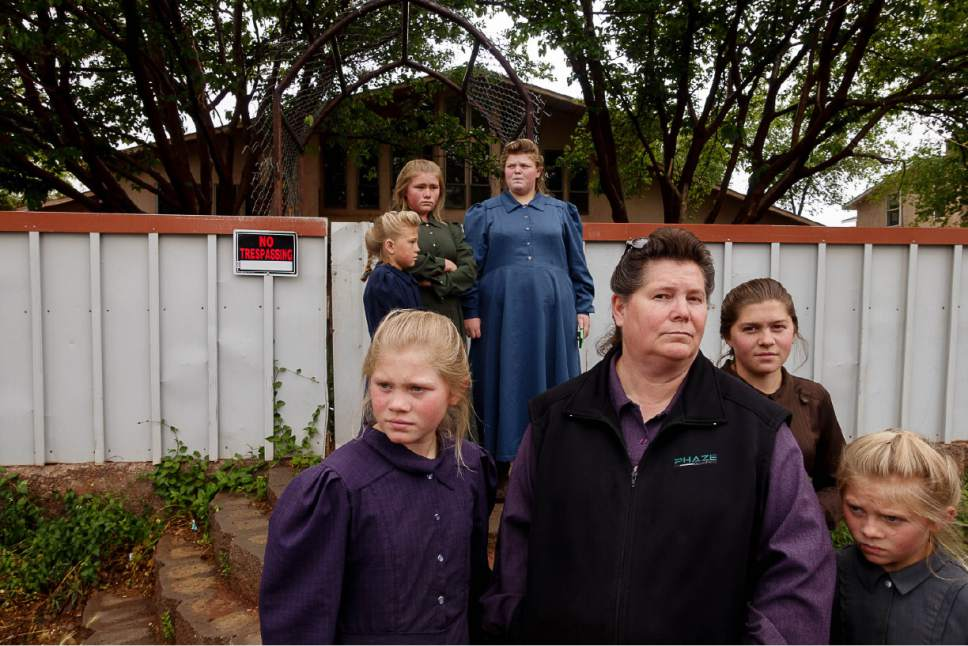 Trent Nelson  |  The Salt Lake Tribune FLDS mother Lydia Bateman with some of her children and grandchildren stand on the sidewalk after being evicted from their Colorado City, AZ, home by the UEP Trust after refusing to sign an occupancy agreement, Wednesday May 10, 2017. Bateman says she had lived in the home since 1978, but her religious beliefs prevent her from cooperating with the trust.
