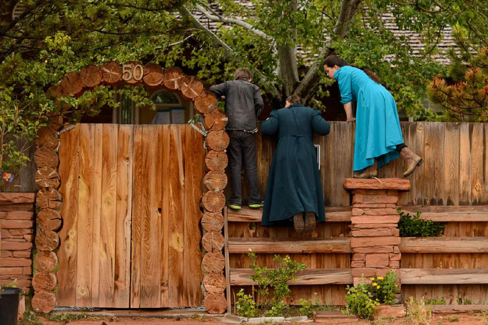 Trent Nelson  |  The Salt Lake Tribune FLDS children look over a wall as the UEP Trust has the locks changed on an FLDS home in Colorado City, AZ, Wednesday May 10, 2017.