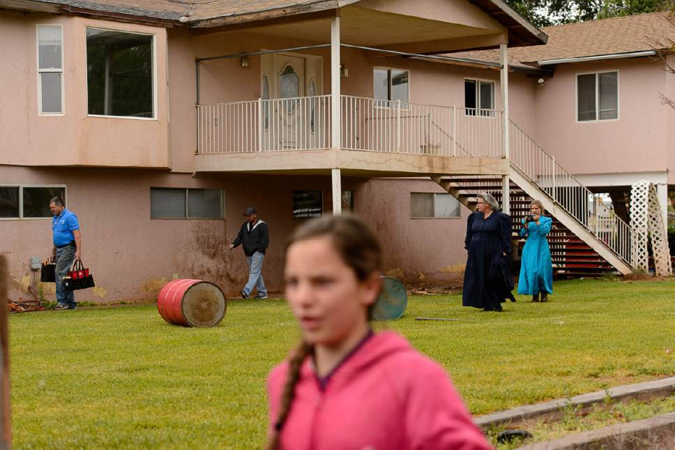 Trent Nelson  |  The Salt Lake Tribune FLDS member Shannon Darger, second from left, looks on as UEP Trust agent Ted Barlow and locksmith Kelvin Holdaway begin to change the locks on her Colorado City, AZ, home, Wednesday May 10, 2017. Like other FLDS members, Darger considers working with the UEP Trust to be against her religious beliefs and has chosen to move her family out of state rather than sign an occupancy agreement with the trust.