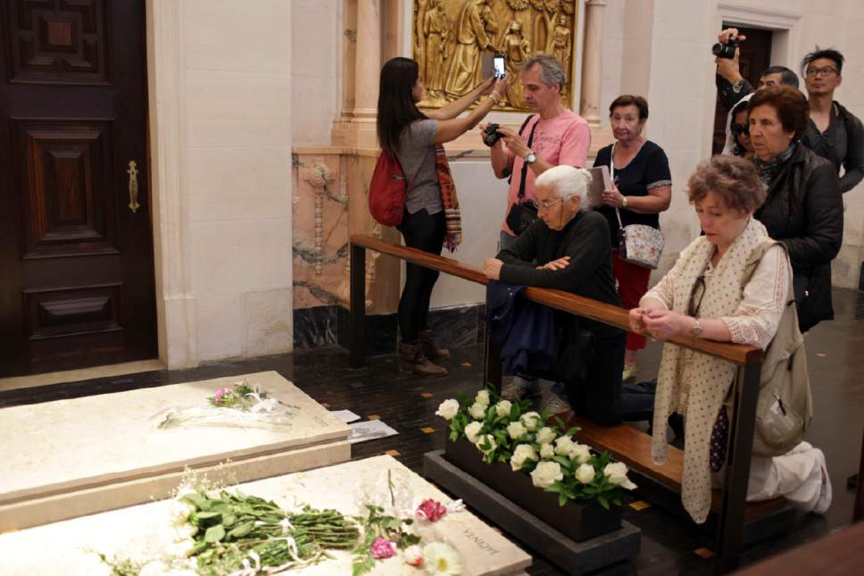 In this photo taken May 4, 2017, a woman in the Basilica of Fatima takes a selfie next to the tombs of Jacinta Marto and Lucia Santos, two of the three shepherd children who say they saw visions of the Virgin Mary 100 years ago, in Fatima, Portugal. Pope Francis is visiting the Fatima shrine on May 12 and 13 to canonize two of the three children, Francisco and Jacinta Marto. (AP Photo/Armando Franca)
