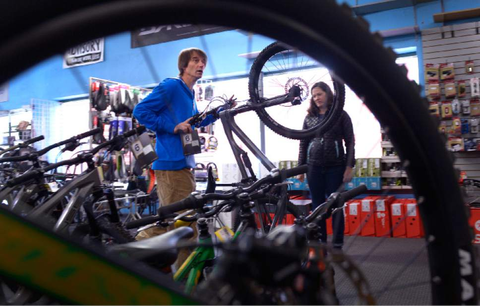 Leah Hogsten  |  The Salt Lake Tribune l-r Tim Metos rolls out a mountain bike for customer Caroline Keeney to test ride Wednesday, May 17, 2017.  After 32 years in business, Tim Metos is closing Wild Rose Sports, a small shop in the Avenues that provided custom mountain bikes and Nordic skiing products.