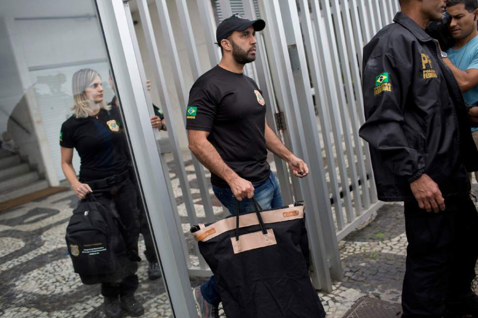 """Federal police officers, carrying seized items, leave the building where Brazilian Sen. Aecio Neves resides, at Ipanema beach in Rio de Janeiro, Brazil, Thursday, May 18, 2017. Brazilian federal police are searching the office and homes of Neves, a top senator and presidential contender. He is being investigated in several corruption cases related to the """"Car Wash"""" probe into kickbacks to politicians. He has denied wrongdoing. (AP Photo/Silvia Izquierdo)"""