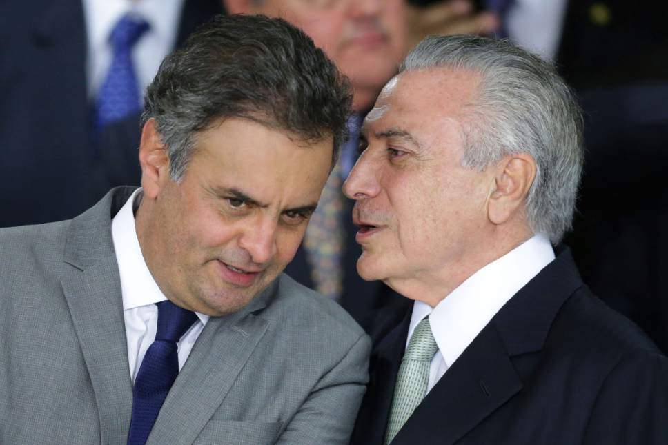 """FILE - In this May 12, 2016 file photo, Brazil's acting President Michel Temer whispers into the ear of Sen. Aecio Neves, at Planalto presidential palace in Brasilia, Brazil. On Thursday, May 18, 2017, Brazilian federal police searched the office and homes of Neves, a top senator and presidential contender. He is being investigated in several corruption cases related to the """"Car Wash"""" probe into kickbacks to politicians. Thursday's searches of Neves' home in Rio de Janeiro and his Brasilia office are fallout from the widespread corruption investigation that has also reached Temer. (AP Photo/Eraldo Peres, File)"""