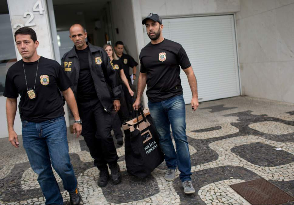 """Federal police officers leave the building where Brazilian Sen. Aecio Neves resides, at Ipanema beach in Rio de Janeiro, Brazil, Thursday, May 18, 2017. Brazilian federal police are searching the office and homes of Neves, a top senator and presidential contender. He is being investigated in several corruption cases related to the """"Car Wash"""" probe into kickbacks to politicians. He has denied wrongdoing. (AP Photo/Silvia Izquierdo)"""