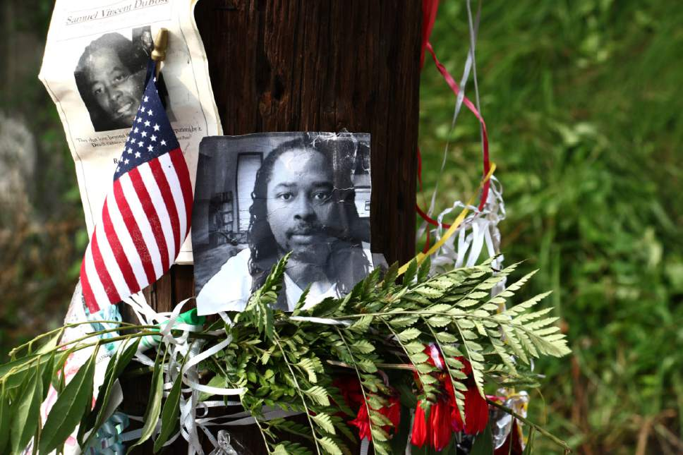 FILE – In this July 29, 2015, file photo, photos of Sam DuBose hang on a pole at a memorial near where he was shot and killed by a University of Cincinnati police officer during a July 19, 2015, traffic stop in Cincinnati. Prosecutors in Ohio say a T-shirt with a Confederate flag emblem worn by Ray Tensing, a white police officer, under his uniform is relevant evidence for countering his claim that he feared for his life when he shot DuBose. The defense says the T-shirt isn't relevant, but could prejudice the jury. (AP Photo/Tom Uhlman, File)