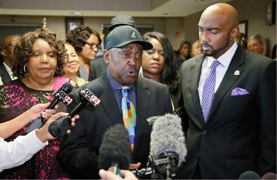 The Rev. Joey Crutcher, father of Terence Crutcher, talks with the media following the verdict in the trial of Betty Shelby in Tulsa, Okla., Wednesday, May 17, 2017. Shelby, a white Oklahoma police officer, was charged with manslaughter in the shooting of Terence Crutcher, an unarmed black man. Shelby was found innocent Wednesday. At left is Leanna Crutcher, the mother of Terence Crutcher and at right is Crutcher family attorney Damario Solomon-Simmons. (AP Photo/Sue Ogrocki)