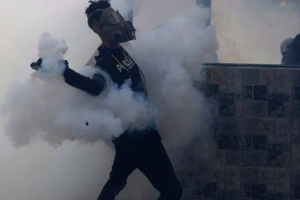 A masked anti-government protester lobs a tear gas canister launched by security forces during clashes in Caracas, Venezuela, Thursday, May 18, 2017. The protest in Caracas comes after a tumultuous 24 hours of looting and protests in the western state of Tachira that led the government to send in troop reinforcements. More than 40 people have been killed in almost two months of unrest in Venezuela. (AP Photo/Fernando Llano)
