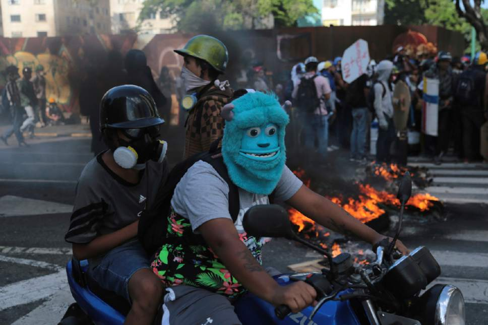 An anti-government protester drives a motorbike wearing a mask depicting the Monster Inc. character Sulley through a barricade set up by fellow protesters, in Caracas, Venezuela, Thursday, May 18, 2017. The protest in Caracas comes after a tumultuous 24 hours of looting and protests in the western state of Tachira that led the government to send in troop reinforcements. More than 40 people have been killed in almost two months of unrest in Venezuela. (AP Photo/Fernando Llano)