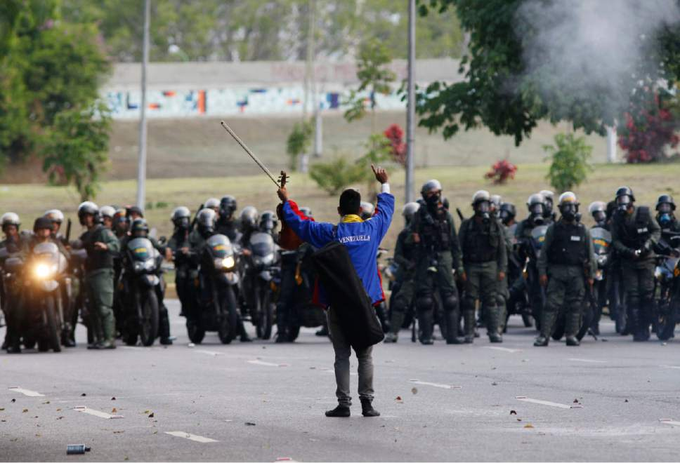An anti-government protester raises his violin before National Guards, as he yells not to shoot at protesters, creating a brief pause during clashes in Caracas, Venezuela, Thursday, May 18, 2017.  The protest in Caracas comes after a tumultuous 24 hours of looting and protests in the western state of Tachira that led the government to send in troop reinforcements, and after almost two months of unrest nationwide in which more than 40 people have been killed. (AP Photo/Ariana Cubillos)