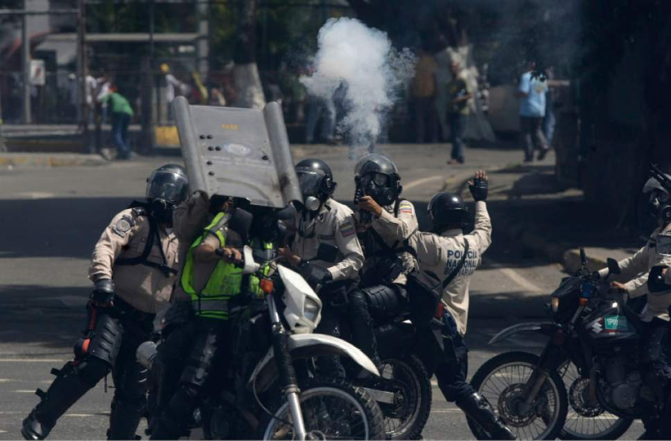 Security forces Anti-government fire tear gas at anti-government protesters in Caracas, Venezuela, Thursday, May 18, 2017. The protest in Caracas comes after a tumultuous 24 hours of looting and protests in the western state of Tachira that led the government to send in troop reinforcements. More than 40 people have been killed in almost two months of unrest in Venezuela. (AP Photo/Fernando Llano)