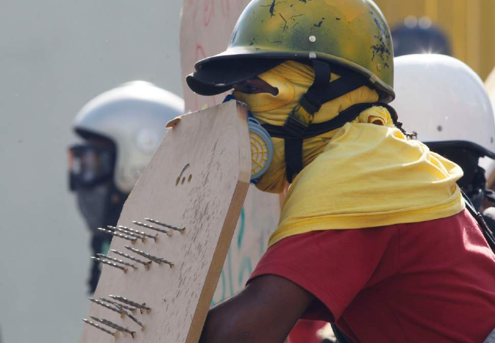 An anti-government protester holds a shield with nails protruding from it as he protects himself from tear gas canisters fired by security forces blocking an opposition march from reaching the Interior Minister in Caracas, Venezuela, Thursday, May 18, 2017. The protest in Caracas comes after a tumultuous 24 hours of looting and protests in the western state of Tachira that led the government to send in troop reinforcements, and after almost two months of unrest nationwide in which more than 40 people have been killed. (AP Photo/Ariana Cubillos)