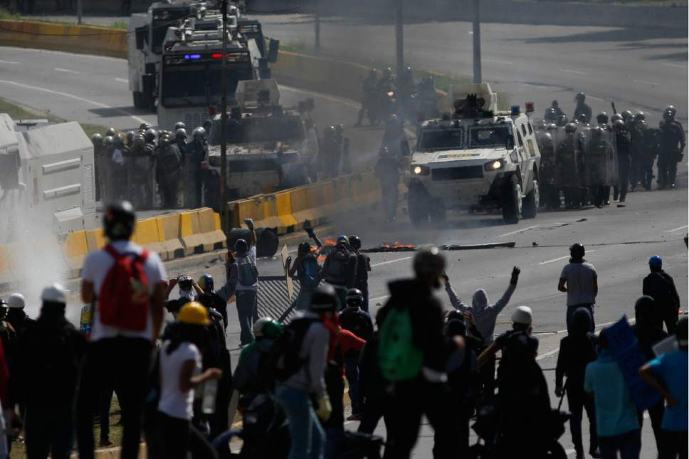 Anti-government protesters face off with security forces blocking an opposition march from reaching the Interior Ministry, in Caracas, Venezuela, Thursday, May 18, 2017. The protest in Caracas comes after a tumultuous 24 hours of looting and protests in the western state of Tachira that led the government to send in troop reinforcements. More than 40 people have been killed in almost two months of unrest in Venezuela. (AP Photo/Ariana Cubillos)