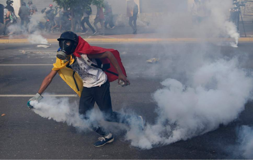 An anti-government protester wearing a Venezuelan flag picks up a tear gas canister fired by security forces trying to disperse an opposition demonstration in Caracas, Venezuela, Thursday, May 18, 2017. The protest in Caracas comes after a tumultuous 24 hours of looting and protests in the western state of Tachira that led the government to send in troop reinforcements, and after almost two months of unrest nationwide in which more than 40 people have been killed. (AP Photo/Ariana Cubillos)