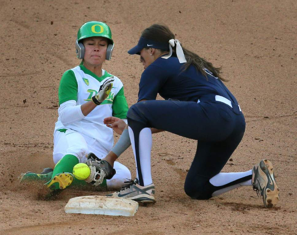 Oregon's Janie Takeda slides safely into second base with a steal, kicking the ball from the glove of BYU second baseman Lauren Bell during an NCAA college softball tournament regional, Thursday, May 14, 2015, in Eugene, Ore. Oregon won 8-0. (Brian Davies/The Register-Guard via AP)