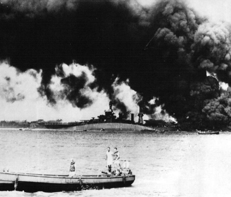 Tribune file photo The USS Oklahoma rests capsized as smoke rises from the USS Maryland shortly after the Japanese attack on Pearl Harbor  Dec. 7, 1941. The U.S. military confirmed Friday that Navy Musician 1st Class Elliot Larson of Utah died when the Oklahoma was sunk.