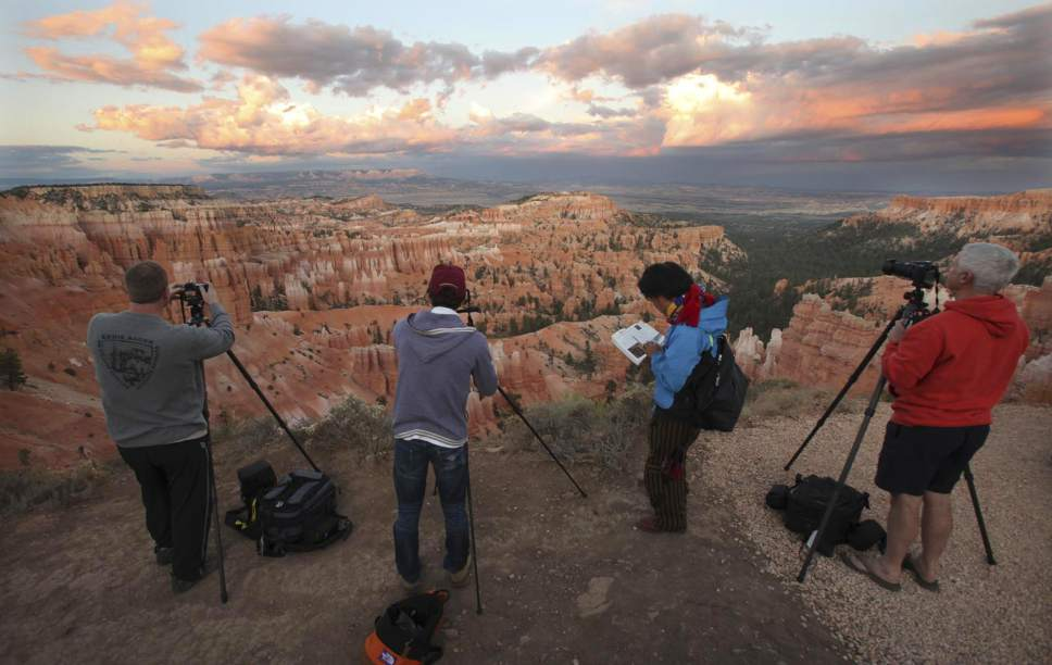 Photographers stand on the Rim Trail photographing the changing sunset light on Bryce Canyon Saturday, Sept., 5, 2009, in Bryce Canyon National Park, Utah.  Both Zion and Bryce were formed millions of years ago when the Earth's crust violently heaved, leaving behind stunning, unique arrays of rock formations.  (AP Photo/Ross D. Franklin)