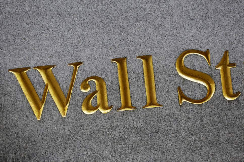 FILE - This Monday, July 6, 2015, file photo shows a sign for Wall Street carved into the side of a building in New York. Stocks are edging higher in early trading on Wall Street, Friday, May 19, 2017, as traders look over a mixed bag of earnings reports. (AP Photo/Mark Lennihan, File)