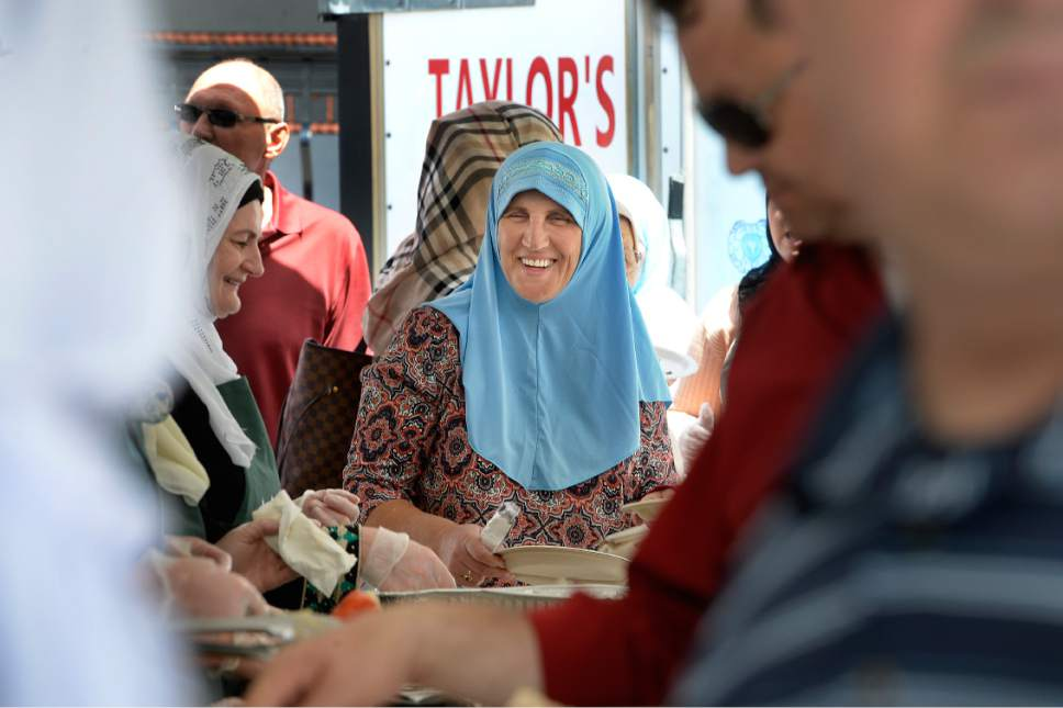 Scott Sommerdorf | The Salt Lake Tribune A woman smiles as she talks with friends who are serving traditional Bosnian food Saturday at the grand opening celebration of the Maryam Mosque at 425 N. 700 East. The day featured tours, music, authentic Bosnian food in celebration of the completion of the extensive remodeling of the mosque by the Islamic Society of Bosniaks in Utah.