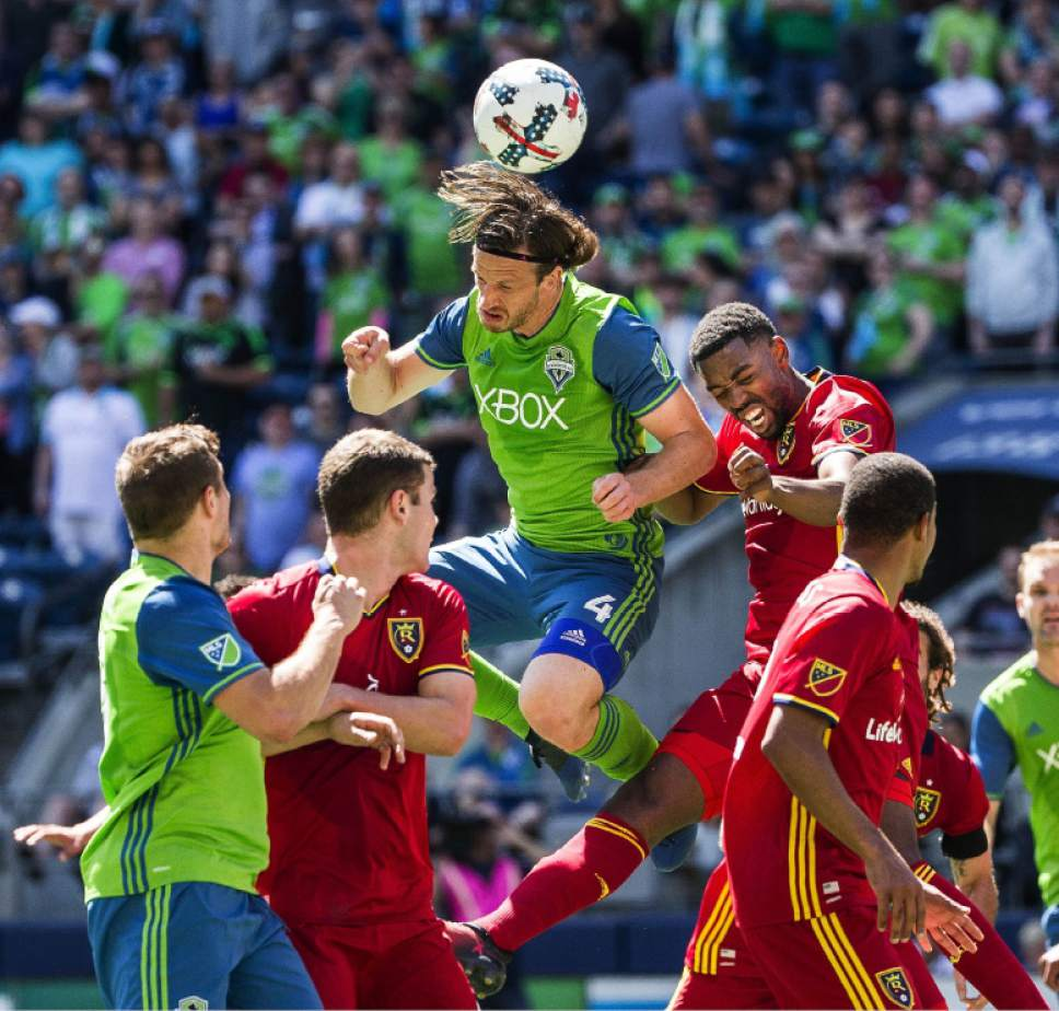Seattle's Gustav Svensson, top center, takes the header but is blocked by Real Salt Lake keeper Nick Rimando in the first half of an MLS soccer match Saturday, May 20, 2017, in Seattle. (Dean Rutz/The Seattle Times via AP)