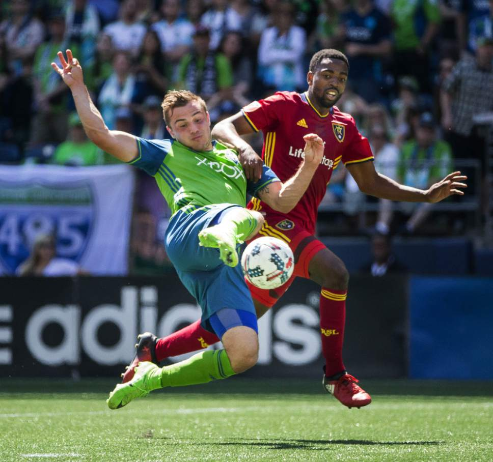 Seattle Sounders Jordan Morris, left, attacks but Real Salt Lake's Aaron Maund gets a hand on his shoulder and disrupts the shot late in the first half of an MLS soccer match Saturday, May 20, 2017, in Seattle. (Dean Rutz/The Seattle Times via AP)