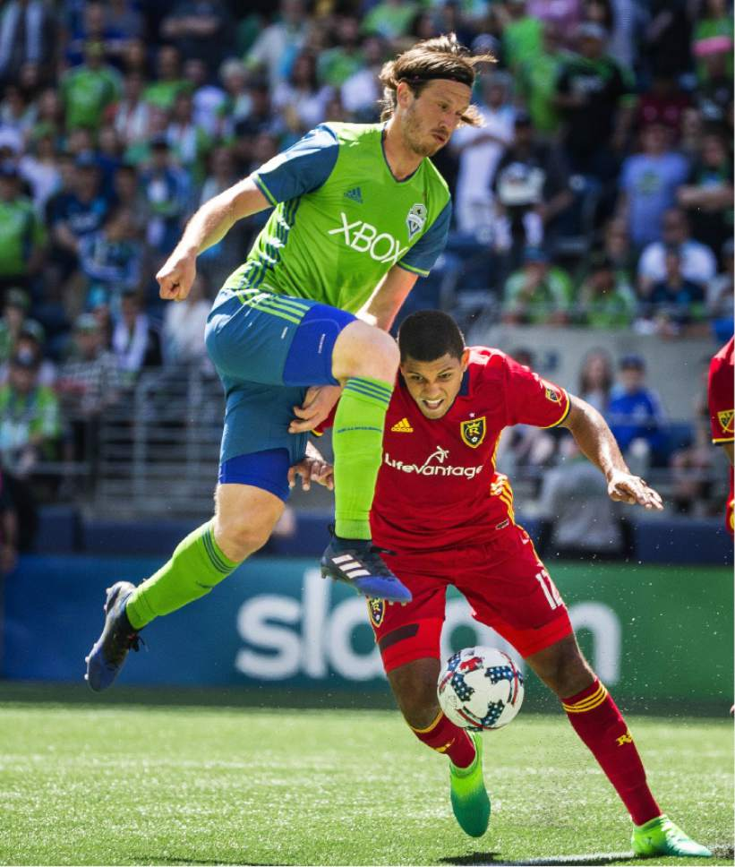 Seattle's Gustav Svensson, top, goes high and Real Salt Lake's Omar Holness goes low as they go after the ball as it reaches the top of the box on the RSL side of the field in the first half of an MLS soccer match Saturday, May 20, 2017, in Seattle. (Dean Rutz/The Seattle Times via AP)