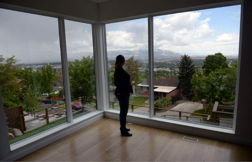 Al Hartmann  |  The Salt Lake Tribune Realtor Cherie Major is silhouetted against the expansive windows of a modern home in Salt Lake City's Capitol Hill neighborhood that  features a sloped, landscaped lot with a spectacular view of the valley.  With a listing price of $1.2 million, it sold in two days.  The Wasatch Front real-estate market is booming if you're a seller.  With a low number of listings on the market, homes in desirable neighborhoods are moving quickly.