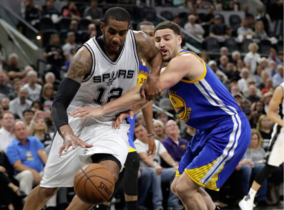 San Antonio Spurs forward LaMarcus Aldridge (12) breaks through the defense of Golden State Warriors' Klay Thompson (11) on a drive to the basket during the second half in Game 4 of the NBA basketball Western Conference finals, Monday, May 22, 2017, in San Antonio. (AP Photo/Eric Gay)