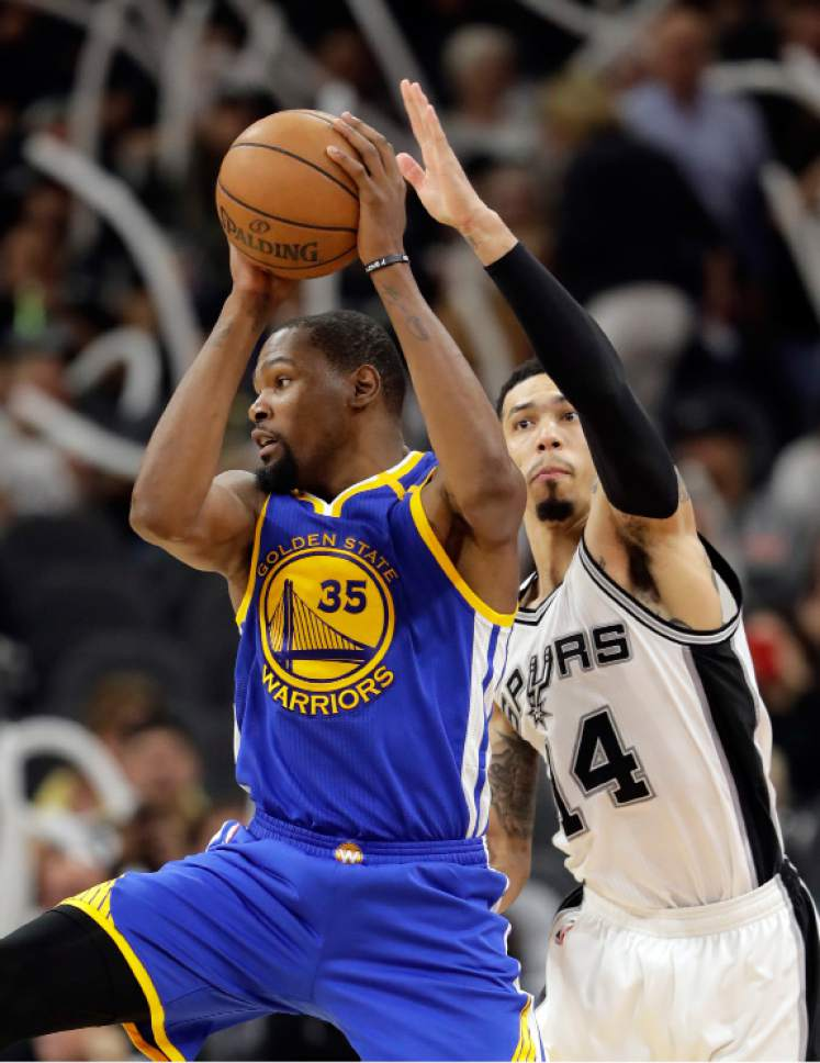 Golden State Warriors forward Kevin Durant (35) controls the ball in front of San Antonio Spurs' Danny Green (14) during the second half in Game 4 of the NBA basketball Western Conference finals, Monday, May 22, 2017, in San Antonio. (AP Photo/Eric Gay)