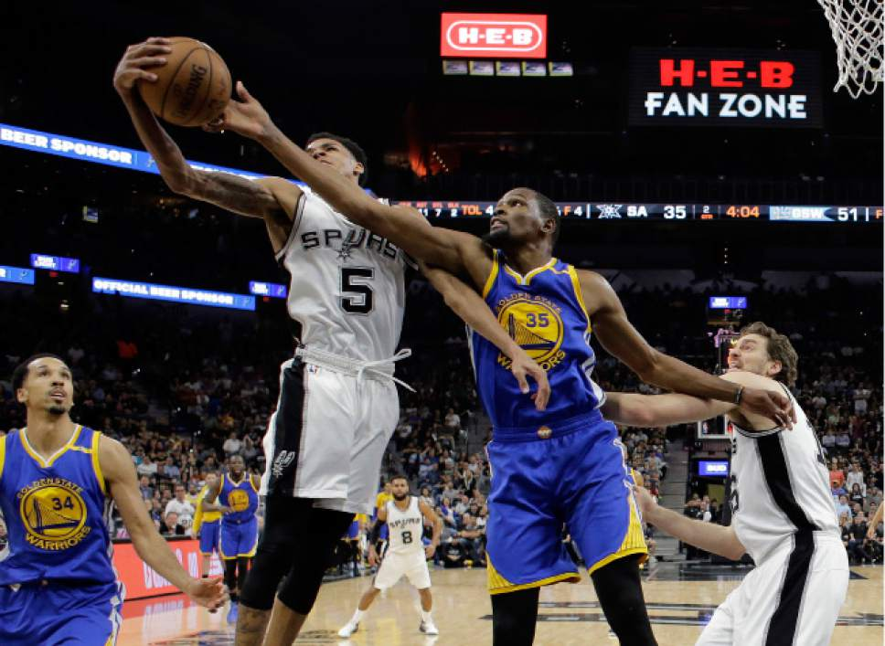 San Antonio Spurs guard Dejounte Murray (5) grabs a rebound in front of Golden State Warriors' Kevin Durant (35) as Shaun Livingston (34) and center Pau Gasol, right, of Spain watch during the first half in Game 4 of the NBA basketball Western Conference finals, Monday, May 22, 2017, in San Antonio. (AP Photo/Eric Gay)