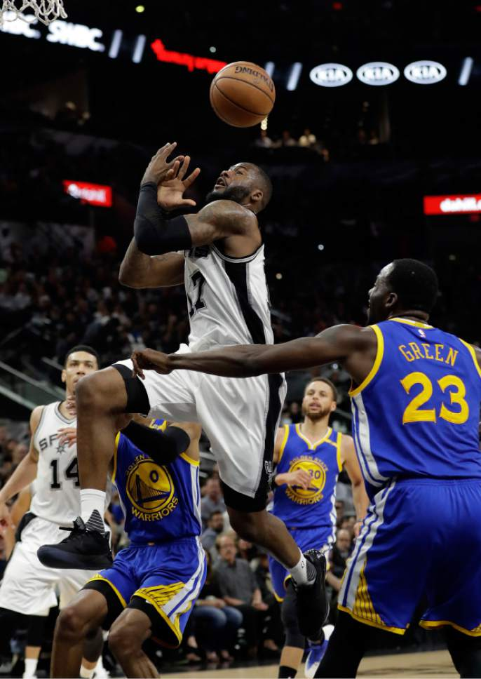 San Antonio Spurs guard Jonathon Simmons (17) has the ball stripped away by Golden State Warriors forward Draymond Green (23) on a drive to the basket during the second half in Game 4 of the NBA basketball Western Conference finals, Monday, May 22, 2017, in San Antonio. (AP Photo/Eric Gay)
