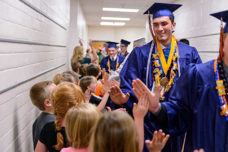 Trent Nelson  |  The Salt Lake Tribune Water Canyon High School graduate Roy Jessop walks a procession of high-fives through Water Canyon Elementary prior to the high school's graduation ceremony in Hildale, Monday May 22, 2017. Two years ago the school had one graduate, this year twenty-five.