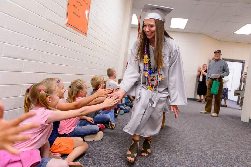 Trent Nelson  |  The Salt Lake Tribune Water Canyon High School graduate Amy Barlow leads a procession of high-fives through Water Canyon Elementary prior to the high school's graduation ceremony in Hildale, Monday May 22, 2017. Two years ago the school had one graduate, this year twenty-five.